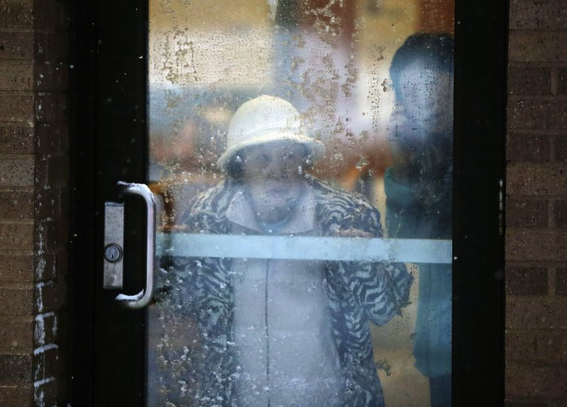 A displaced resident looks out a door after a deadly fire at a high-rise apartment building Wednesday, Nov. 27, 2019, in Minneapolis. (David Joles/Star Tribune via AP)