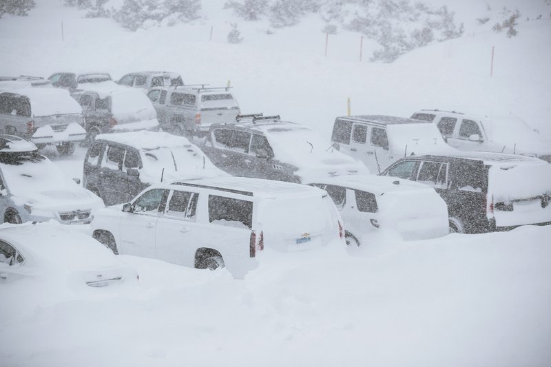 This Tuesday, Nov. 27, 2019 photo provided by the Mammoth Mountain Ski Area shows parked SUVs covered in snow at Mammoth Mountain in Mammoth Mountain, Calif. Blizzard conditions have closed Interstate 5 south of Ashland, Oregon, all the way to the California state line. The Siskiyou Summit at the border on I-5, typically one of the more perilous sections of freeway along the West Coast corridor in wintery weather, had seen 6 inches of new snow with 10 inches packed on the roadside. (Peter Morning/Mammoth Mountain Ski Area via AP)