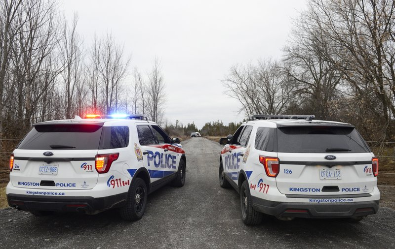 Two Kingston Police cars block a road leading to the site of a fatal plane crash in Kingston, Ontario, on Thursday, Nov. 28, 2019. (Sean Kilpatrick/The Canadian Press via AP)