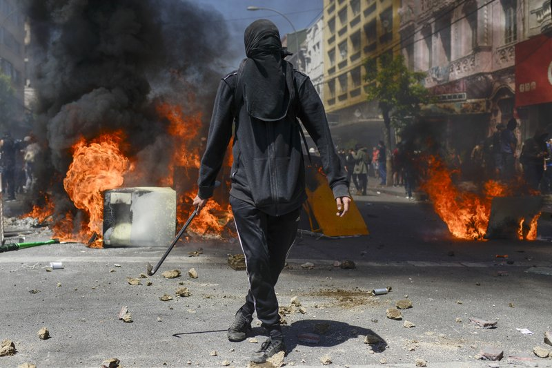 An anti-government demonstrator stands in front of a burning barricade in Valparaiso, Chile, on Oct. 24, 2019. (AP Photo / Matias Delacroix)