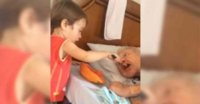 Little boy feeds grandpa in the mouth and moves the world