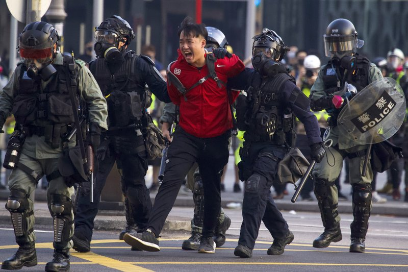 A pro-democracy protester shouts after being detained by policemen during a rally in Hong Kong, Sunday, Dec. 1, 2019. A huge crowd took to the streets of Hong Kong on Sunday, some driven back by tear gas, to demand more democracy and an investigation into the use of force to crack down on the six-month-long anti-government demonstrations. (AP Photo/Ng Han Guan)