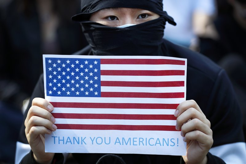 A protester holds a placard carrying an American flag during a rally in Hong Kong, Sunday, Dec. 1, 2019. Hong Kong protesters carrying American flags and banners appealing to President Donald Trump are rallying in the semi-autonomous Chinese territory. (AP Photo/Vincent Thian)
