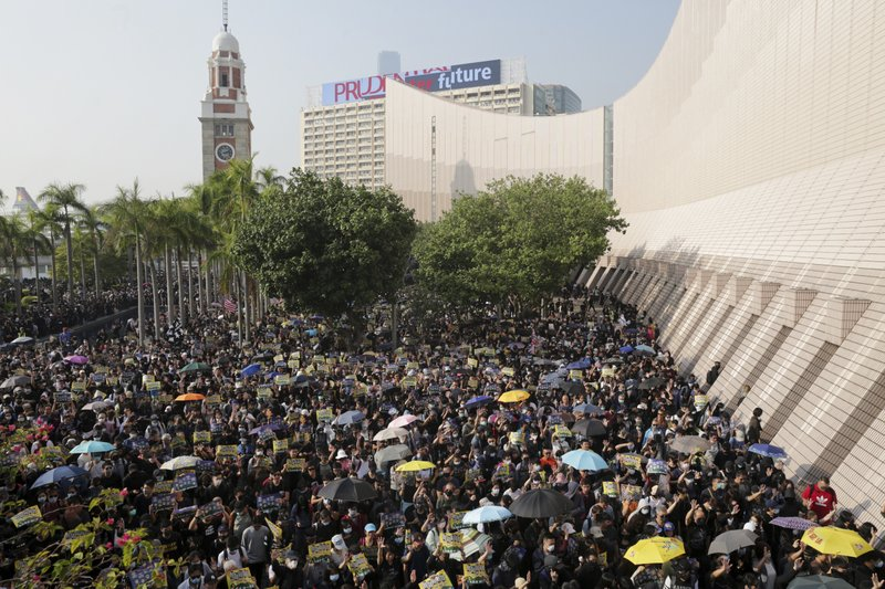 Pro-democracy protesters gather in a rally in Hong Kong, Sunday, Dec. 1, 2019. A huge crowd took to the streets of Hong Kong on Sunday, some driven back by tear gas, to demand more democracy and an investigation into the use of force to crack down on the six-month-long anti-government demonstrations. (Max Au/HK01 via AP)