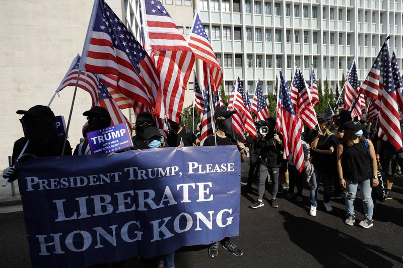 Protesters carrying banner and American flags march to U.S. Consulate during a rally in Hong Kong, Sunday, Dec. 1, 2019. Hong Kong protesters carrying American flags and banners appealing to President Donald Trump rallied in the semi-autonomous Chinese territory. (AP Photo/Vincent Thian)