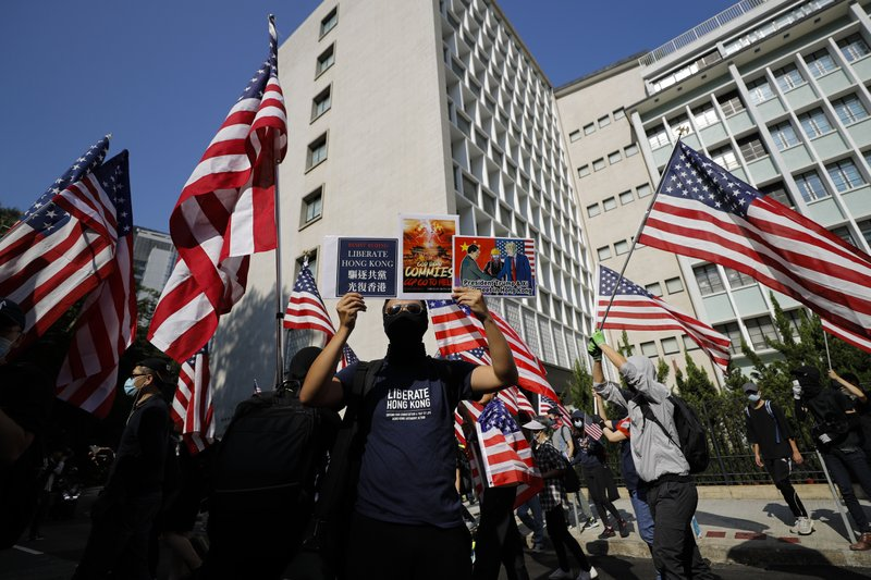 Protesters carrying American flags march to U.S. Consulate during a rally in Hong Kong, Sunday, Dec. 1, 2019. Hong Kong protesters carrying American flags and banners appealing to President Donald Trump rallied in the semi-autonomous Chinese territory. (AP Photo/Vincent Thian)