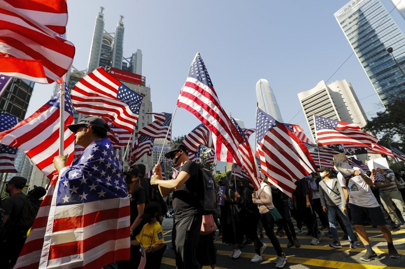 Protesters march to U.S. Consulate during a rally in Hong Kong, Sunday, Dec. 1, 2019. Hong Kong protesters carrying American flags and banners appealing to President Donald Trump are rallying in the semi-autonomous Chinese territory. (AP Photo/Vincent Thian)