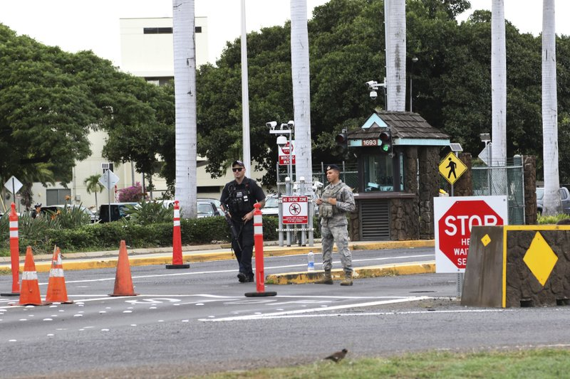 Security stand outside the main gate at Joint Base Pearl Harbor-Hickam, Wednesday, Dec. 4, 2019, in Hawaii. A shooting at Pearl Harbor naval shipyard in Hawaii left at least one person injured Wednesday, military and hospital officials said. (AP Photo/Caleb Jones)