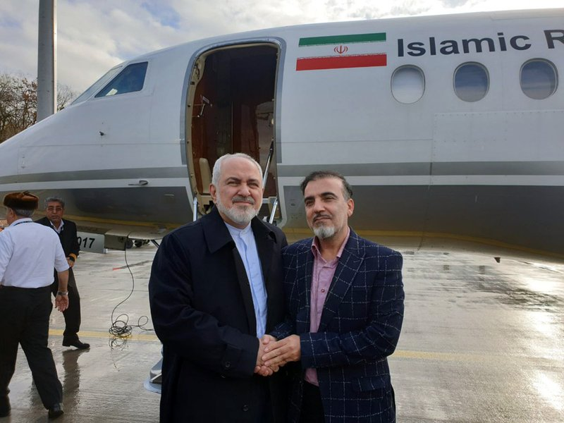 In this photo released on twitter account of Iran's Foreign Minister Mohammad Javad Zarif , Zarif, left, shakes hand with Iranian scientist Massoud Soleimani prior to leaving Zurich, Switzerland for Tehran, Iran, Saturday, Dec. 7, 2019. Iran and the U.S. conducted a prisoner exchange Saturday that saw a detained Princeton scholar released for an Iranian scientist held by America, marking a rare diplomatic breakthrough between Tehran and Washington after months of tensions. (Javad Zarif twitter account via AP)