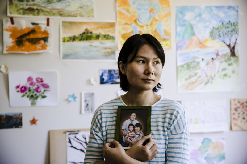 "FILE - In this Wednesday, May 9, 2018 file photo, Hua Qu, the wife of  detained Chinese-American Xiyue Wang, poses for a photograph with a portrait of her family in Princeton, N.J. Iran's foreign minister says a detained Princeton graduate student will be exchanged for an Iranian scientist held by the U.S. Mohammed Javad Zarif made the announcement on Twitter on Saturday, Dec. 7, 2019. The trade involves graduate student Xiyue Wang and scientist Massoud Soleimani. Wang was sentenced to 10 years in prison in Iran for allegedly ""infiltrating"" the country and sending confidential material abroad. His family and Princeton strongly denied the claims. (AP Photo/Matt Rourke, File)"