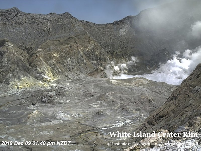 In this image released by GeoNet, tourists can be seen near the volcano's crater Monday, Dec. 9, 2019, on White Island, New Zealand. Prime Minister Jacinda Ardern says about 100 tourists were on or near White Island when the volcano erupted and some of them are missing. (GNS Science via AP)