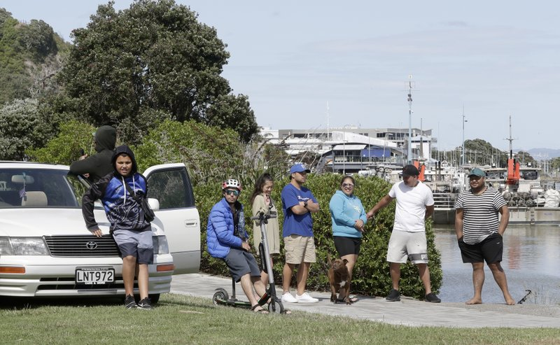 People wait on the waterfront in Whakatane, New Zealand, Tuesday, Dec. 10, 2019. A volcanic island in New Zealand erupted Monday Dec. 9 in a tower of ash and steam while dozens of tourists were exploring the moon-like surface, killing multiple people and leaving many more missing.(AP Photo/Mark Baker)