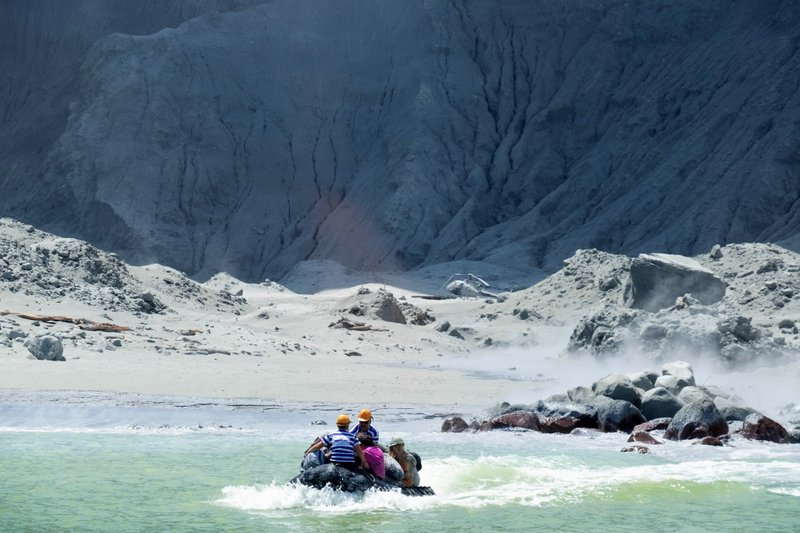 This Dec. 9, 2019, photo provided by Michael Schade shows the rescuers' boat leaving White Island following the eruption of the volcano, New Zealand. Unstable conditions continued to hamper rescue workers from searching for people missing and feared dead after the volcano off the New Zealand coast erupted in a towering blast of ash and scalding steam while dozens of tourists explored its moon-like surface. (Michael Schade via AP)