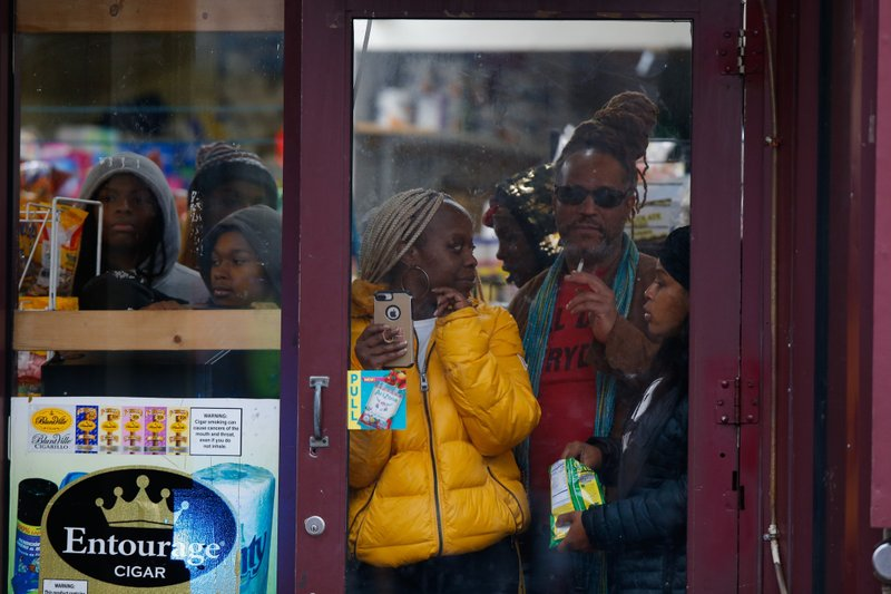 Bystanders look out from a store as law enforcement arrives at the scene following reports of gunfire, Tuesday, Dec. 10, 2019, in Jersey City, N.J. AP Photo/Eduardo Munoz Alvarez)