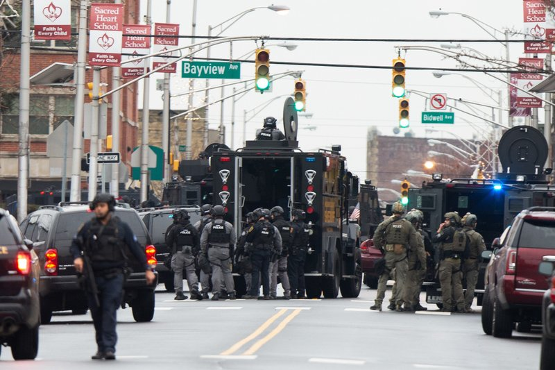 Law enforcement gathers near the scene following reports of gunfire, Tuesday, Dec. 10, 2019, in Jersey City, N.J.  AP Photo/Eduardo Munoz Alvarez)