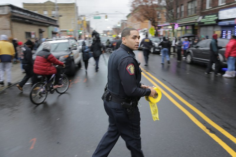 A police officer pushes pedestrians back from the scene of a shooting in Jersey City, N.J., Tuesday, Dec. 10, 2019. Authorities say multiple, including a police officer and three bystanders, have been killed in a furious gun battle that filled the streets of Jersey City, New Jersey, with the sound of heavy gunfire for hours. The dead include two suspects. (AP Photo/Seth Wenig)