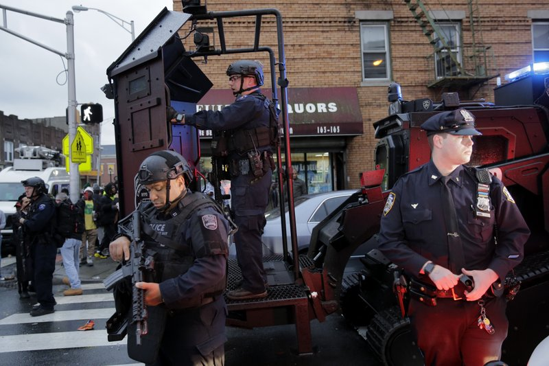 Emergency responders move heavy equipment near the scene of a shooting in Jersey City, N.J., Tuesday, Dec. 10, 2019. Authorities say multiple, including a police officer and three bystanders, have been killed in a furious gun battle that filled the streets of Jersey City, New Jersey, with the sound of heavy gunfire for hours. The dead include two suspects. (AP Photo/Seth Wenig)