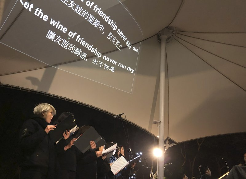 In this Tuesday, Dec. 10, 2019 photo, lyrics are projected on a canopy as a theater troupe performs Les Miserables in at an outdoor event space in Hong Kong. A Hong Kong theater troupe is making audiences weep by touring a stirring production of 'Les Miserables.' Based on Victor Hugo's tale of rebellion in 19th-century France, the rousing music and lyrics of struggle and resistance struck chords with audience members emotionally and physically drained after six months of protests that have convulsed the city. (AP Photo/John Leicester)