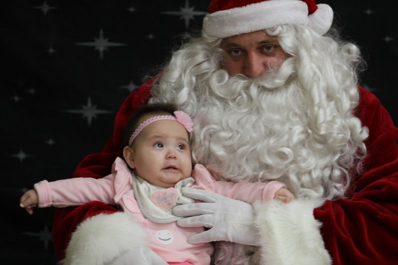 This Dec. 3, 2019, photo shows 6-month-old Rebecca Ilmar having her photo taken with Santa Claus in Napakiak, Alaska. The Alaska National Guard brought its Operation Santa Claus to the western Alaska community, which is being severely eroded by the nearby Kuskokwim River. (AP Photo/Mark Thiessen)
