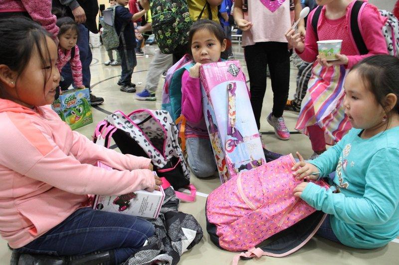 HOLD FOR USE WITH STORY MOVING TUESDAY NIGHT FOR WEDNESDAY, DEC. 11, 2019-This Dec. 3, 2019, photo shows Krysta Lexie Kau'aq, left, Michelle Nelson, middle and Jessilyn Oscar, right, admire the gifts they got from Santa Claus during his visit to Napakiak, Alaska. The Alaska National Guard brought its Operation Santa Claus to the western Alaska community, which is being severely eroded by the nearby Kuskokwim River. (AP Photo/Mark Thiessen)