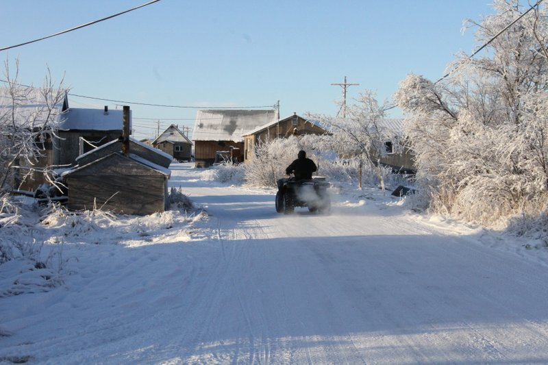 This Dec. 3, 2019, photo shows a man driving a four-wheeler down a street in Napakiak, Alaska. The Alaska National Guard brought its Operation Santa Claus to the western Alaska community, which is being severely eroded by the nearby Kuskokwim River. (AP Photo/Mark Thiessen)