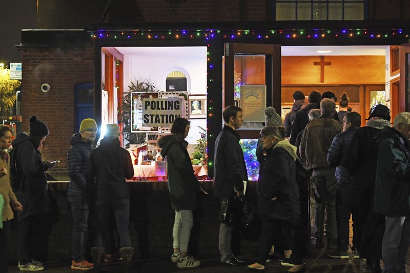 Voters queue outside St Andrews Church polling station in Balham, south London, just hours before voting closes for the 2019 General Election, Thursday, Dec. 12, 2019. Britons who have endured more than three years of wrangling over their country's messy divorce from the European Union cast ballots Thursday in an election billed as a way out of the Brexit stalemate in this deeply divided nation. (Victoria Jones/PA via AP)