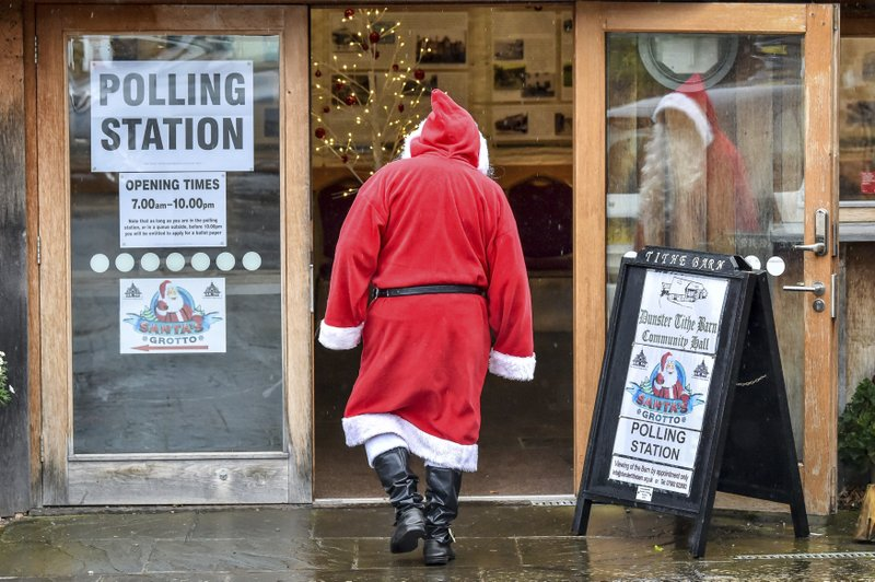 A man dressed as Father Christmas enters his grotto at the Dunster Tithe Barn near Minehead, Somerset, England which is being used as a polling station in the 2019 general election, Thursday Dec. 12, 2019. U.K. voters were deciding Thursday who they want to resolve the stalemate over Brexit in a parliamentary election seen as one of the most important since the end of World War II. (Ben Birchall/PA via AP)