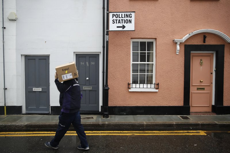 A man carries a box away from a polling station in London, Thursday, Dec. 12, 2019. The general election in Britain on Thursday will bring a new Parliament to power and may lead to a change at the top if Prime Minister Boris Johnson's Conservative Party doesn't fare well with voters. Johnson called the early election in hopes of gaining lawmakers to support his Brexit policy. (AP Photo/Thanassis Stavrakis)
