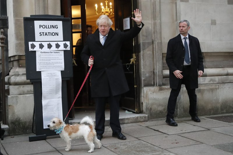 Britain's Prime Minister and Conservative Party leader Boris Johnson with his dog Dilyn as he leaves after voting in the general election at Methodist Central Hall, Westminster, London, Thursday, Dec. 12, 2019. The general election in Britain on Thursday will bring a new Parliament to power and may lead to a change at the top if Prime Minister Boris Johnson's Conservative Party doesn't fare well with voters. Johnson called the early election in hopes of gaining lawmakers to support his Brexit policy. (AP Photo/Frank Augstein)