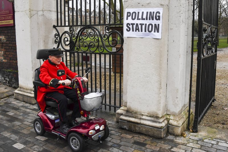 Chelsea Pensioners arrive at the polling station to vote in the General Election, in the Chelsea area of London, Thursday, Dec. 12, 2019. Voting is underway across the country in a general election that may resolve the stalemate over Brexit, widely seen as one of the most decisive votes in modern times. (AP Photo/Alberto Pezzali)