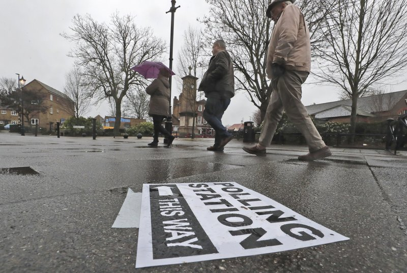 A polling station signpost lies on the pavement as voters approach a polling station in Twickenham, England, Thursday, Dec. 12, 2019. British voters are deciding who they want to resolve the Brexit conundrum in an election seen as one of the most important since the end of World War II.  (AP Photo/Frank Augstein)