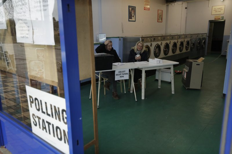 A presiding officer and a clerk drink cups of tea next to heaters to keep warm as they sit inside their polling station at Ace Laundrette in Oxford, England, Thursday, Dec. 12, 2019. Voting is underway across the country in a general election that may resolve the stalemate over Brexit, widely seen as one of the most decisive votes in modern times. (AP Photo/Matt Dunham)