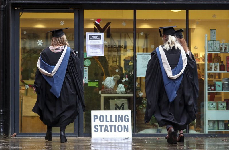 Students from the University of Reading arrive to vote in the general election, in Reading, England, Thursday Dec. 12, 2019.  The U.K. is voting Thursday for they want to resolve the stalemate over Brexit, in a parliamentary election widely seen as one of the most decisive in modern times.(Steve Parsons/PA via AP)