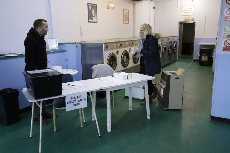 A presiding officer and a clerk stand with heaters to keep warm inside their polling station at Ace Launderette in Oxford, England, Thursday, Dec. 12, 2019.  Voting is underway across the country in a general election that may resolve the stalemate over Brexit, widely seen as one of the most decisive votes in modern times. (AP Photo/Matt Dunham)
