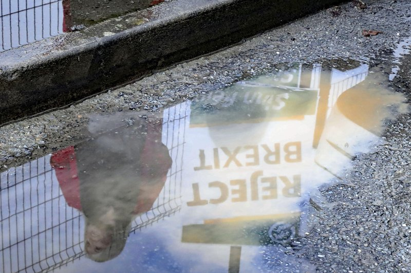 Sinn Fein Deputy leader Michelle O'Neill reflected in a puddle after casting her vote in the General Election at Patrick's Primary School in Clonoe, County Tyrone, Northern Ireland, Thursday, Dec. 12, 2019. U.K. voters were deciding Thursday who they want to resolve the stalemate over Brexit in a parliamentary election seen as one of the most important since the end of World War II. (Niall Carson/PA via AP)