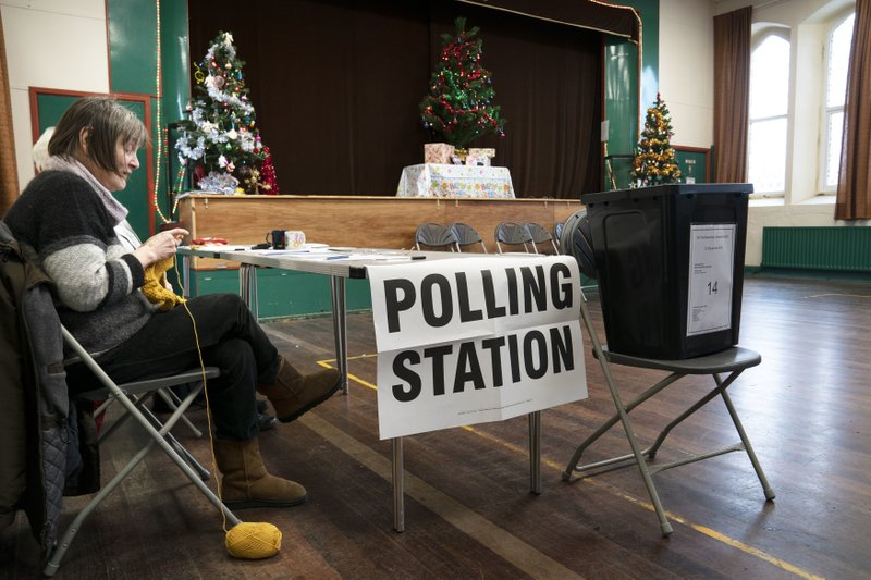 Chris Johnson, 62, does her knitting while awaiting people to vote at the polling station in Nenthead Village Hall in Cumbria, England Thursday Dec. 12, 2019. U.K. voters were deciding Thursday who they want to resolve the stalemate over Brexit in a parliamentary election seen as one of the most important since the end of World War II. (Owen Humphreys/PA via AP)