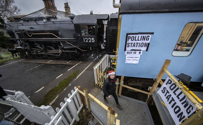 Wensleydale Railway employee Teresa Chapman is pictured with the Polar Express in the background, next to a polling station in a railway carriage as voters go to the polls, in Leeming Bar, North Yorkshire, England, Thursday, Dec. 12, 2019. Britain is holding an early election in wintry December, with a number of strange locations put in use as polling places. Among the places where Britons cast their ballots Tuesday were a car dealership, a laundrette, a Christmas grotto and of course some pubs. There were a few problems, including flooding at one location. (Danny Lawson/PA via AP)