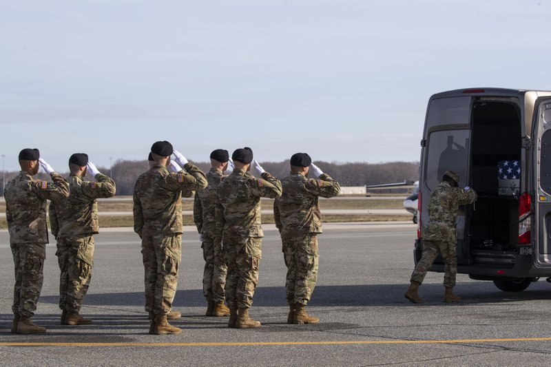 An Army carry team slaues a transfer case containing the remains of U.S. Army Sgt. 1st Class Michael Goble, as U.S. Air Force Tech. Sgt. Shaquita Darby closes the door, Wednesday, Dec. 25, 2019, at Dover Air Force Base, Del. According to the Department of Defense, Goble, of Washington Township, N.J., assigned to the 7th Special Forces Group, died while supporting Operation Freedom's Sentinel. (AP Photo/Alex Brandon)