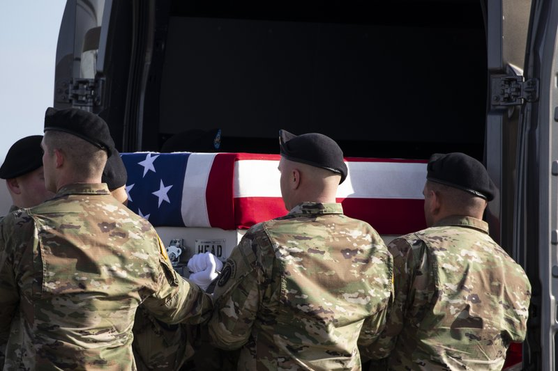 An Army carry team loads a transfer case containing the remains of U.S. Army Sgt. 1st Class Michael Goble, Wednesday, Dec. 25, 2019, at Dover Air Force Base, Del. According to the Department of Defense, Goble, of Washington Township, N.J., assigned to the 7th Special Forces Group, died while supporting Operation Freedom's Sentinel. (AP Photo/Alex Brandon)