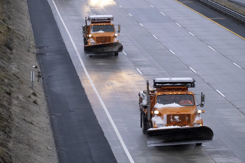 Plows covered with snow return to Castaic, Calif., as snow on the Grapevine closed the freeway Thursday, December 26, 2019. The CHP had no estimate as to when the freeway would re-open.  (David Crane/The Orange County Register via AP)