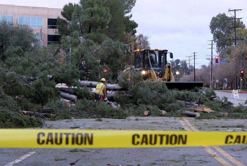 Workers remove a tree that fell across Burbank Blvd. at Canoga Ave. in Woodland Hills, Calif., following a night of steady rain, on Thursday, December 26, 2019. (Dean Musgrove/The Orange County Register via AP)