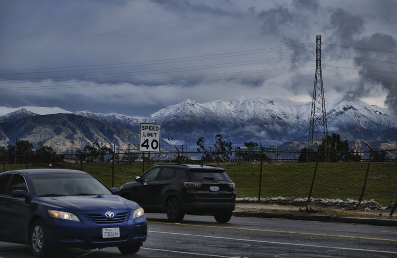 Morning commuters drive with the hills in the background in the Sun Valley section of Los Angeles on Thursday, Dec. 26, 2019. A powerful winter storm brought a deluge of rain and snow to Southern California, triggering tornado warnings and bringing post-Christmas travel to a halt on major routes. (AP Photo/Richard Vogel)