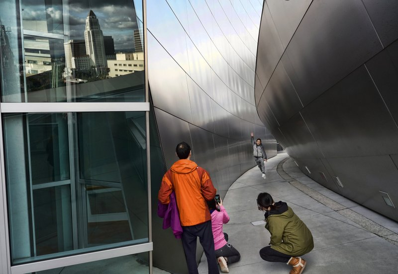 Heavy storm clouds are reflected in a window over Los Angeles City Hall, left, while Chinese tourists take photos along a walkway at the Walt Disney Concert Hall on Thursday, Dec. 26, 2019. A cold and blustery winter storm unleashed a deluge of rain and snow on Southern California, triggering tornado warnings and snarling post-Christmas travel on major routes. (AP Photo/Richard Vogel)