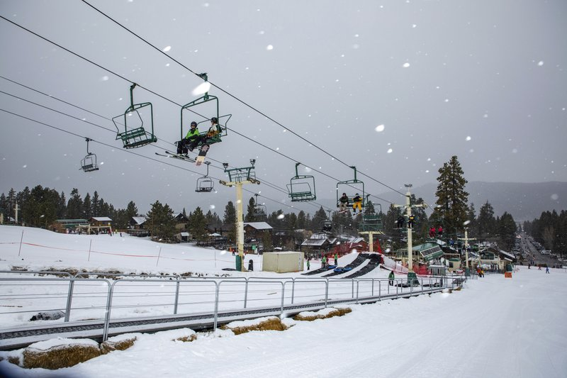 In this photo provided by Big Bear Mountain Resort, snowboard and ski enthusiasts ride a lift to the slopes at Big Bear Mountain Resort in Big Bear, Calif., Monday, Dec. 23, 2019. Winter weather advisories are in effect for the interior mountains of Los Angeles and Ventura counties, where a foot more of snow is expected at elevations above 7,000 feet and lesser amounts down to 5,000 feet. (Jared Meyer/Big Bear Mountain Resort via AP)