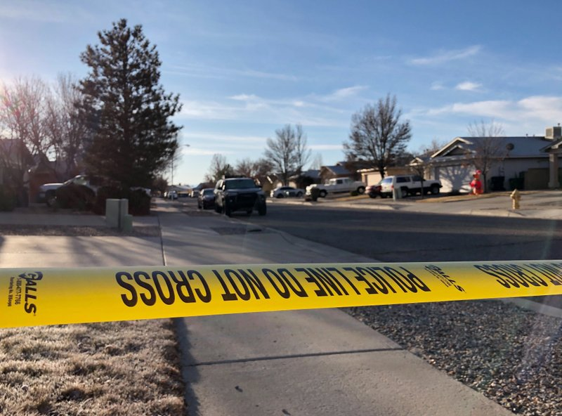 Police have a residential street cordoned off as detectives investigate the deaths of four people found Christmas Day inside a home in Rio Rancho, N.M., on Thursday, Dec. 26, 2019.  All of the victims appeared to have suffered gunshot wounds, police said in a statement posted on Facebook. Police did not identify the victims or say whether a suspect or suspects have been identified. (AP Photo/Susan Montoya Bryan)