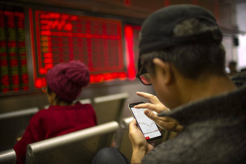 A Chinese investor uses his smartphone as he monitors stock prices at a brokerage house in Bejiing, Thursday, Dec. 26, 2019. Shares are mostly higher in Asia with many world markets closed for Christmas holidays. (AP Photo/Mark Schiefelbein)