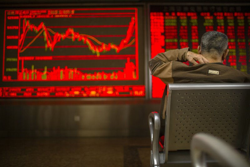A Chinese investor monitors stock prices at a brokerage house in Bejiing, Thursday, Dec. 26, 2019. Shares are mostly higher in Asia with many world markets closed for Christmas holidays. (AP Photo/Mark Schiefelbein)