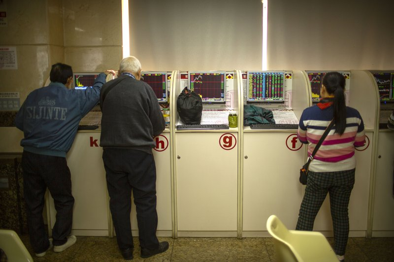 Chinese investors use computer terminals as they monitor stock prices at a brokerage house in Bejiing, Thursday, Dec. 26, 2019. Shares are mostly higher in Asia with many world markets closed for Christmas holidays. (AP Photo/Mark Schiefelbein)