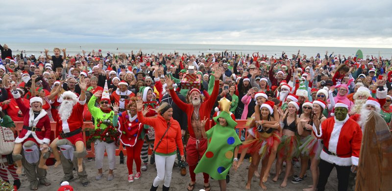 Thousands turned out to watch hundreds of Surfing Santas catch some waves in Cocoa Beach for the 10th annual Surfing Santas event Tuesday, Dec. 24, 2019. Ten years ago George Trosset, his son George Jr. and his daughter-in-law went surfing in Santa and Christmas costumes behind their house on Christmas Eve. The event has grown and now raises money for two local non profits - Grind for Life, which helps with financial assistance for cancer patients, and the Florida Surf Museum. (Malcolm Denemark/Florida Today via AP)