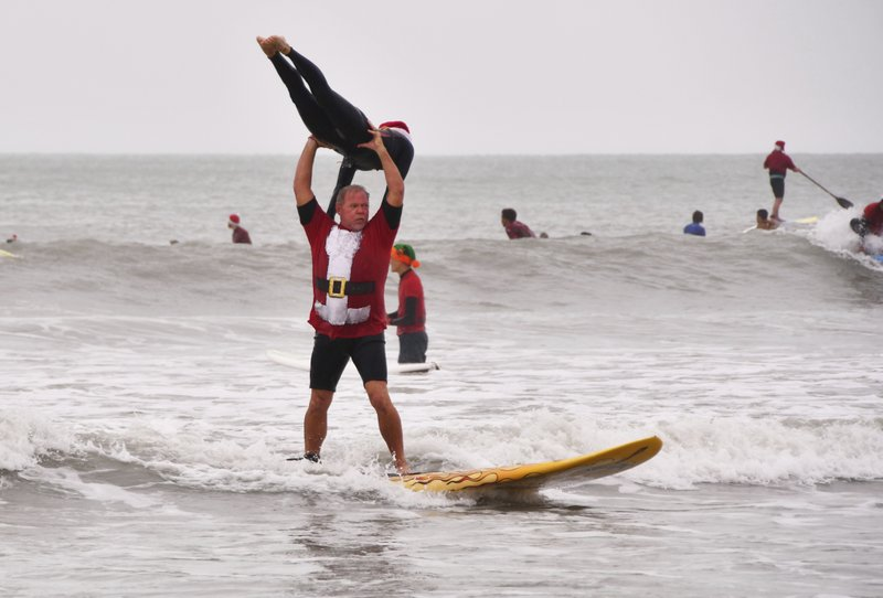 Bear and Cindy Woznick pulled off some tandem surfing Tuesday, Dec. 24, 2019. Thousands turned out to watch hundreds of Surfing Santas catch some waves in Cocoa Beach for the 10th annual Surfing Santas event. Ten years ago George Trosset, his son George Jr. and his daughter-in-law went surfing in Santa and Christmas costumes behind their house on Christmas Eve. The event has grown and now raises money for two local non profits - Grind for Life, which helps with financial assistance for cancer patients, and the Florida Surf Museum. (Malcolm Denemark/Florida Today via AP)